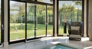 Large black aluminum slide doors nature and indoor pool view and clear mirror