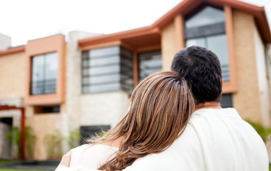 A couple standing in front of a house.
