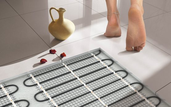 Person walking barefoot on clean white tiles view of the under tile heat installation element