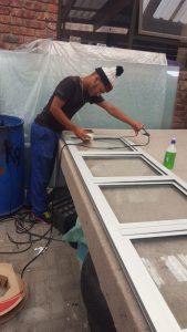 Worker measuring and manufacturing aluminium windows