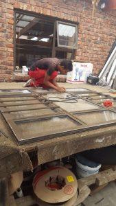 Manual worker assembling PVC doors and windows.