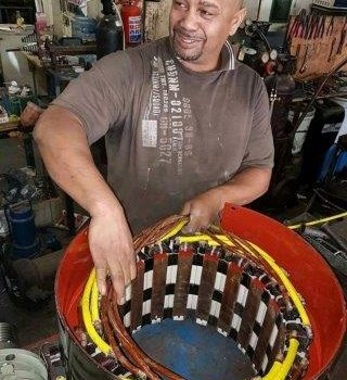 A man working with winding copper coil.