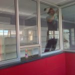 Worker measuring and working with aluminium windows