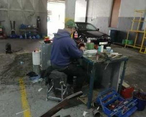A man sitting and working in a workshop.